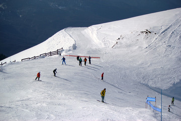 Skiers and snowboarders riding on a ski slope in Sochi mountain resort snowy winter