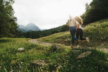 Cheerful women running on mountain road