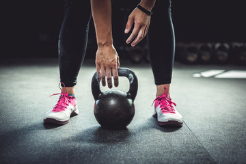 Woman in gym holding a kettlebell. Working Out at Crossfit.
