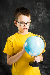 Boy spinning and looking at globe