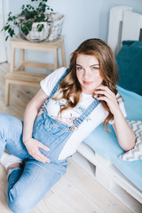 красивая светловолосая беременная девушка в джинсовом комбинезоне beautiful blond pregnant girl in a denim jumpsuit