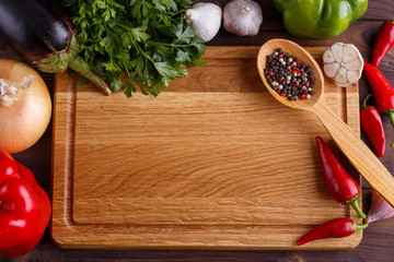 Chopping board, vegetables, herbs and spices in wooden spoon, ingredients for food and cuisine. Kitchen background, cooking concept, free space for advertisement or text.