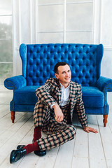 Fashionable cheerful person in an elegant suit sits on a blue sofa
