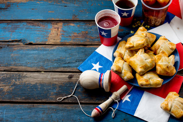 Chilean independence day concept. fiestas patrias. Chilean typical dish and drink on independence day party, 18 september. Mini empanadas, mote con huesillo, wine with toasted flour, chicha and