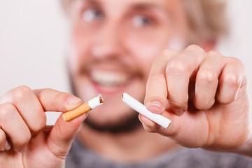 Smilling man is breaking a cigarette