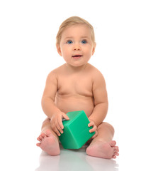 Infant child baby boy toddler playing holding green brick toy in hands on a floor