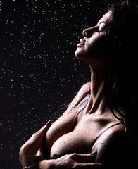 Young beautiful woman sitting under the rain water drops water shower splash