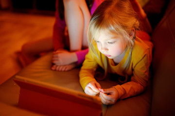 Adorable little girl playing with a digital tablet in a dark room. Children having fun together at home.