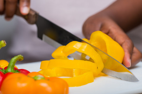 Hands cutting bell peppers with knife, food preparation