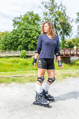 Young woman rollerblading outside in summer park with knee and elbow pads looking by bridge
