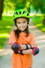 Portrait of a girl with arms crossed in a protective helmet and protective pads for roller skating