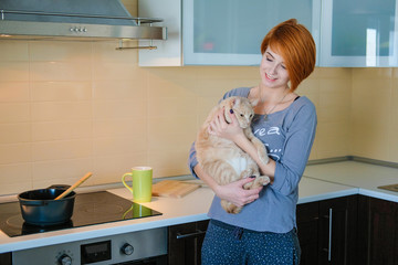 Girl hipster in home clothes hugging a pet. Red head girl in pajamas standing in the kitchen and holding red fluffy cat.