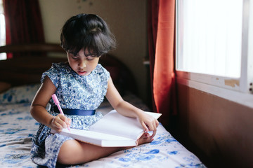 A little girl writes in a notebook with a pen