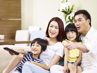 happy asian family sitting on couch watching TV at home.