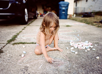 child draws with chalk