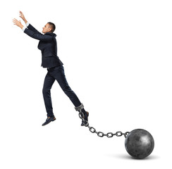 A businessman shackled to a huge iron ball leaps up and tries to catch something above.
