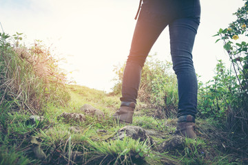 Close-up of female hiker feet walking on forest trail. Active woman backpacker traveling on the nature.