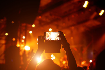 People holding smartphones and taking photo on concert stage