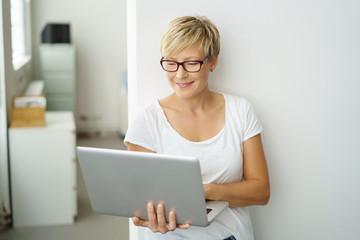 frau steht im büro und schaut auf ihren laptop