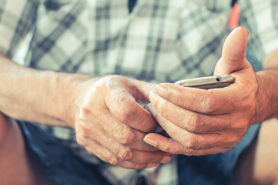 Close up of an elderly man hand using mobile smart phone