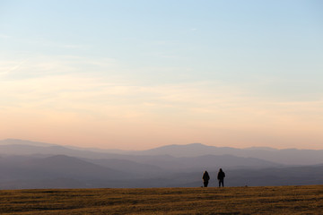 A couple on top of a mountain at near sunset, with warm and soft tones and distant hills and mountains