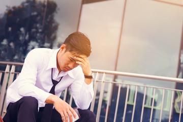 Worried businessman sitting in front of company and thinking about working future.