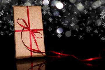 красивый подарок с красной лентой на черном фоне