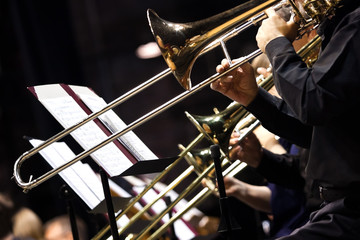 Trombones in the hands of musicians in the orchestra closeup