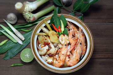 Tom Yum Kung Shrimp clear soup and herb ingredient on wooden background, Thai food, still life.