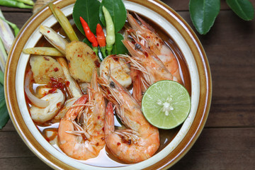 Tom Yum Kung Shrimp clear soup  is decorated with lime, red pepper, culantro, lemongrass, galangal, chili paste and mushroom on wooden background, Hot and spicy food, Thailand nation food.