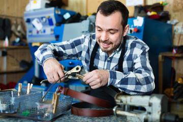 Male worker making hole in belt in specialized workshop