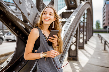 Lifestyle portrait of a young stylish woman with smartphone outdoors on the old iron bridge