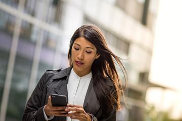 Businesswoman outdoors using smartphone