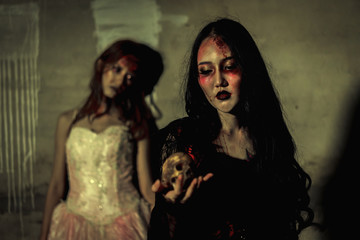Witch death the ghost holding skull and zombie in dress women with blood skin is screaming darkness and nightmare background, horror of scary fear on hell is monster devil girl in halloween festival