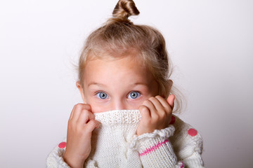child girl wearing knited sweater hiding her face in collar look