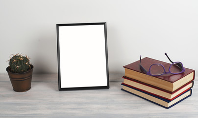Photo frame on wooden table next to books. Decor.