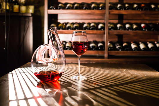 Wine carafe and wine glass on a wine shelves background.