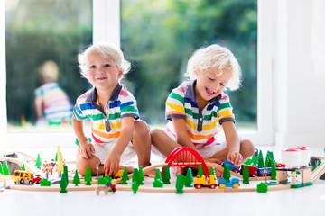 Wall Mural - Children play wiht toy train. Kids wooden railway.