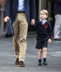 Prince George holds his father Britain's Prince William's hand as he arrives on his first day of school at Thomas's school in Battersea, London