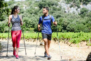 beautiful young couple sport fitness nordic walking and exercising together outdoor summer countryside forest Wall mural