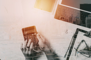 top view of businessman hand working with finances about cost and calculator and latop with mobile phone on withe desk in modern office with building exposure