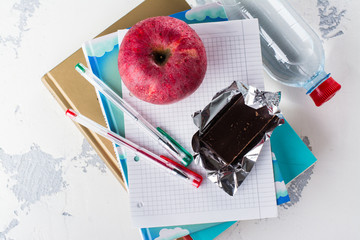 School exams concept. Books, apple, chocolate bar over white table. Space for text
