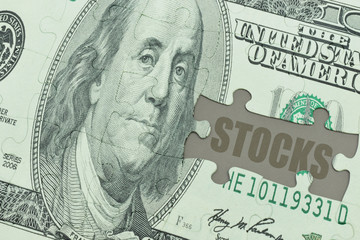 puzzle with the dollar banknote and the text stocks.