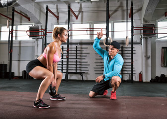 Fit woman doing squats with kettlebell and assistance of trainer at gym