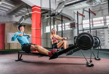 Fitness couple training on row machine at cross gym