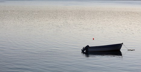 Small fishing boat on calm ocean early morning