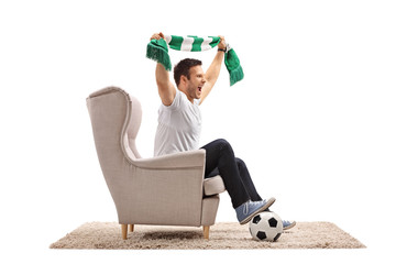 Excited soccer fan with football and scarf cheering