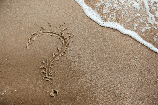 question mark sign in sand beach