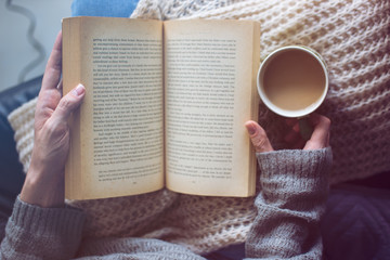 a woman is reading a book and holding coffee