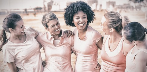 Laughing women wearing pink for breast cancer